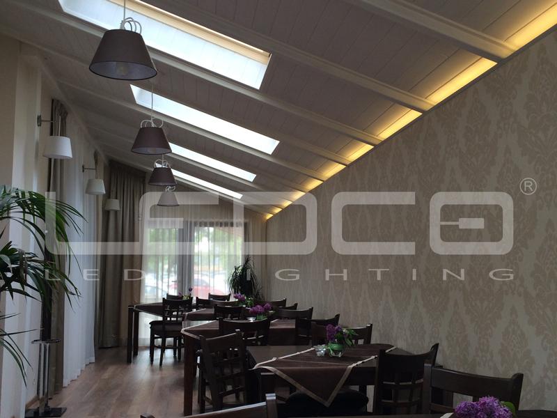 Dekorečné LED podsvietenie a elegantné závesné lapmy Lucide v reštaurácii.