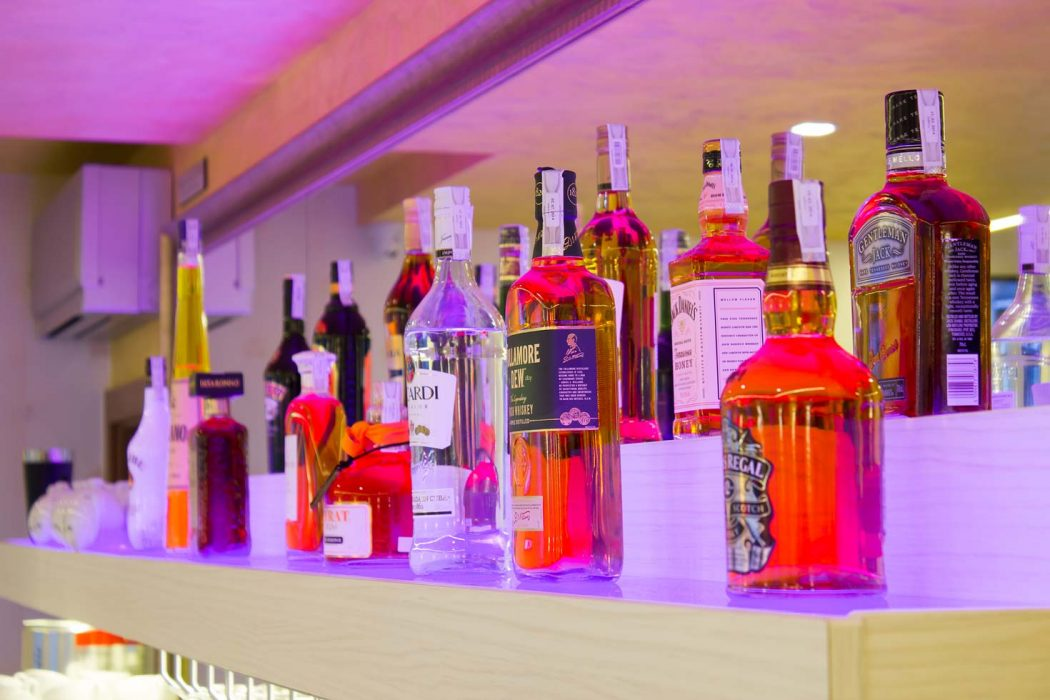 Colourful illumination of the bottles in the bar